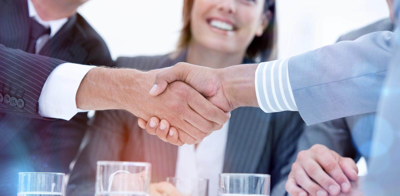 Smiling business people closing a deal. Against a white background royalty free stock image