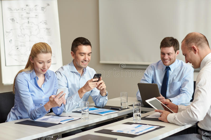 Smiling business people with gadgets in office royalty free stock images