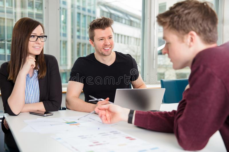 Smiling Business People Looking At Colleague Explaining Chart At royalty free stock images