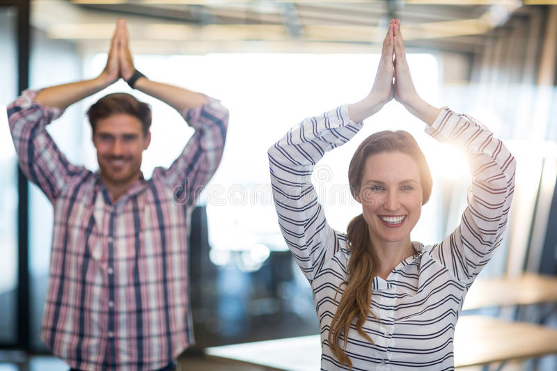 Smiling business people performing yoga in office stock photo