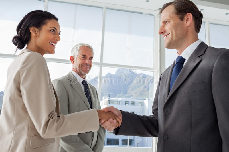 Smiling business people shaking hands with smiling colleague behind them stock photos