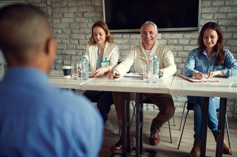 smiling business people team talking about candidate at job interview. royalty free stock image