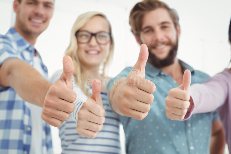Smiling business people with thumbs up stock photos