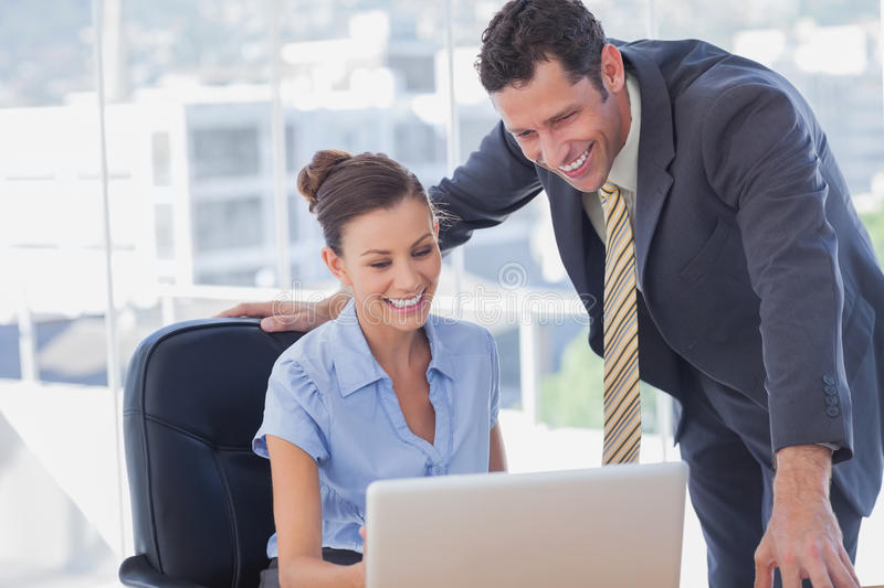 Smiling business people working together with the same laptop royalty free stock images