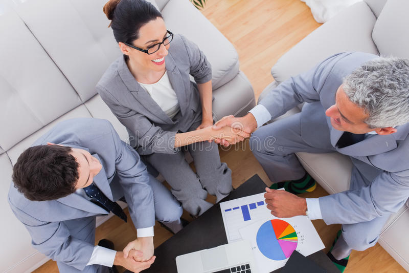 Smiling business shaking hands during meeting. On sofa at office royalty free stock images