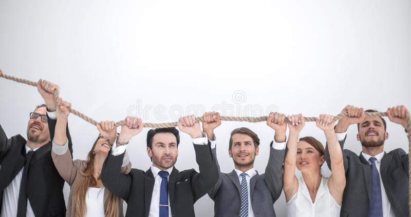 Smiling business team is holding on to a strong rope. Photo with copy space stock photos