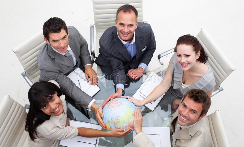 Smiling business team holding the world stock photography