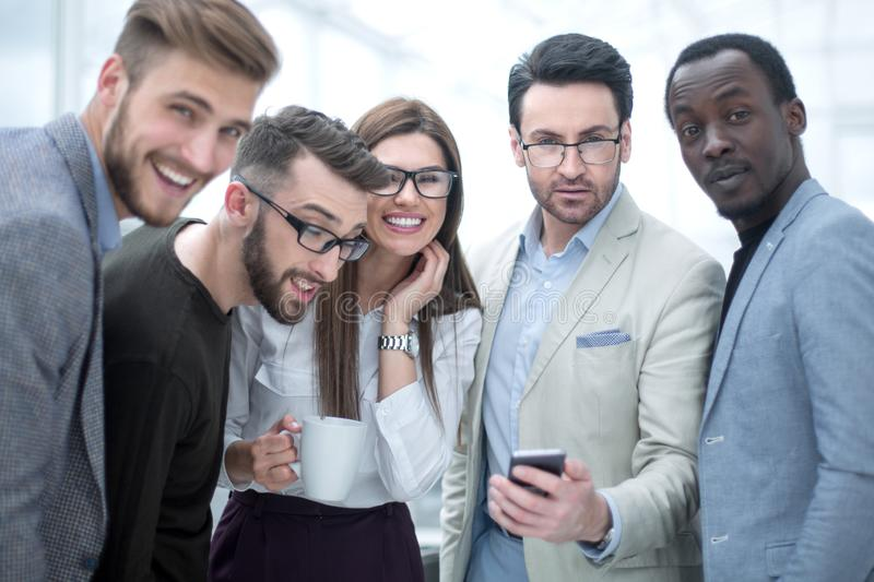 Smiling business team looking at the smartphone screen stock photo