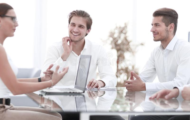 Smiling business team sitting at the Desk. stock photos