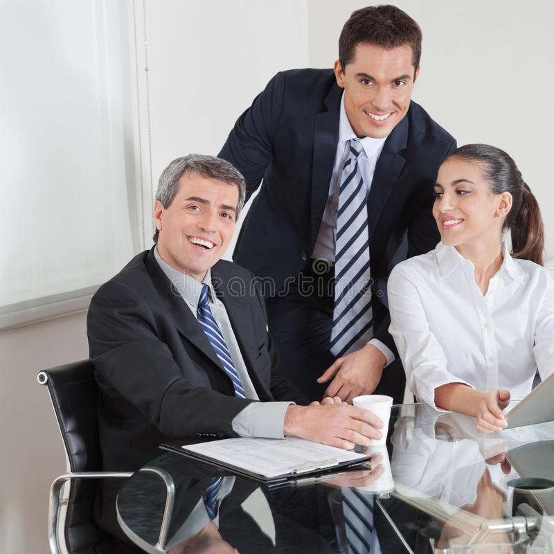 Download Smiling Business Team At Table Stock Photo - Image: 27545256