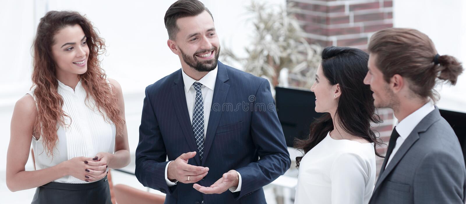 Smiling business team talking, standing in office royalty free stock image