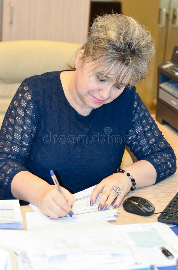 Smiling business woman. A beautiful business-woman working in the office signing documents royalty free stock images