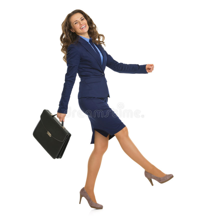 Smiling business woman with briefcase cheerfully going sideways. Full length portrait of smiling business woman with briefcase cheerfully going sideways stock photography