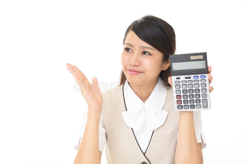 Smiling business woman. Business woman holding a calculator royalty free stock photo