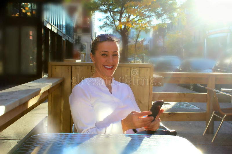 Smiling business woman in the city. Smiling business woman at outdoor terrace cafe texting or reading news on smart phone, while waiting for the waiter. City stock images