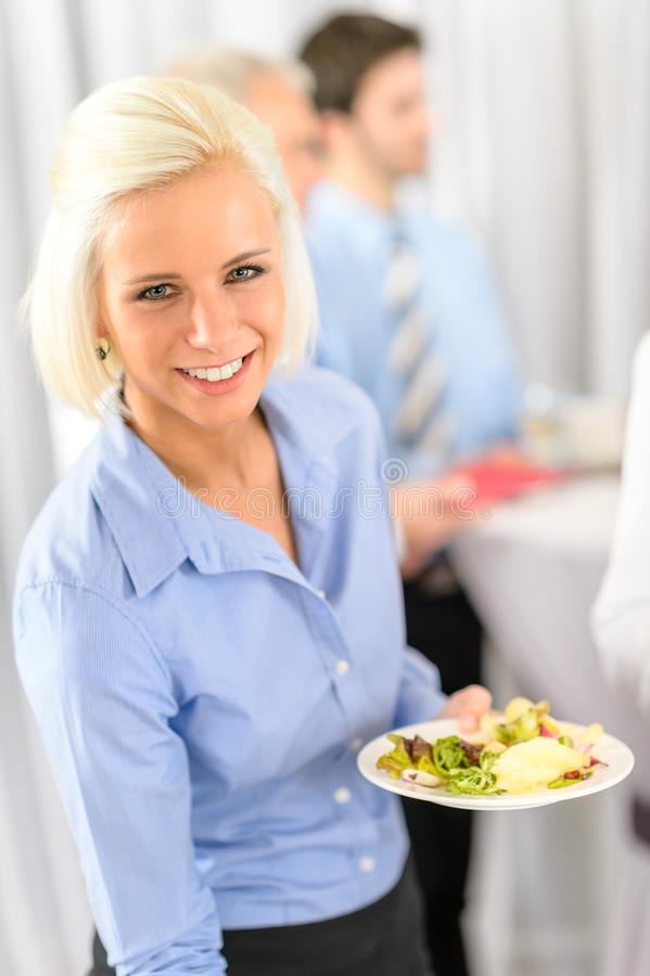 Smiling business woman during company lunch buffet stock photography
