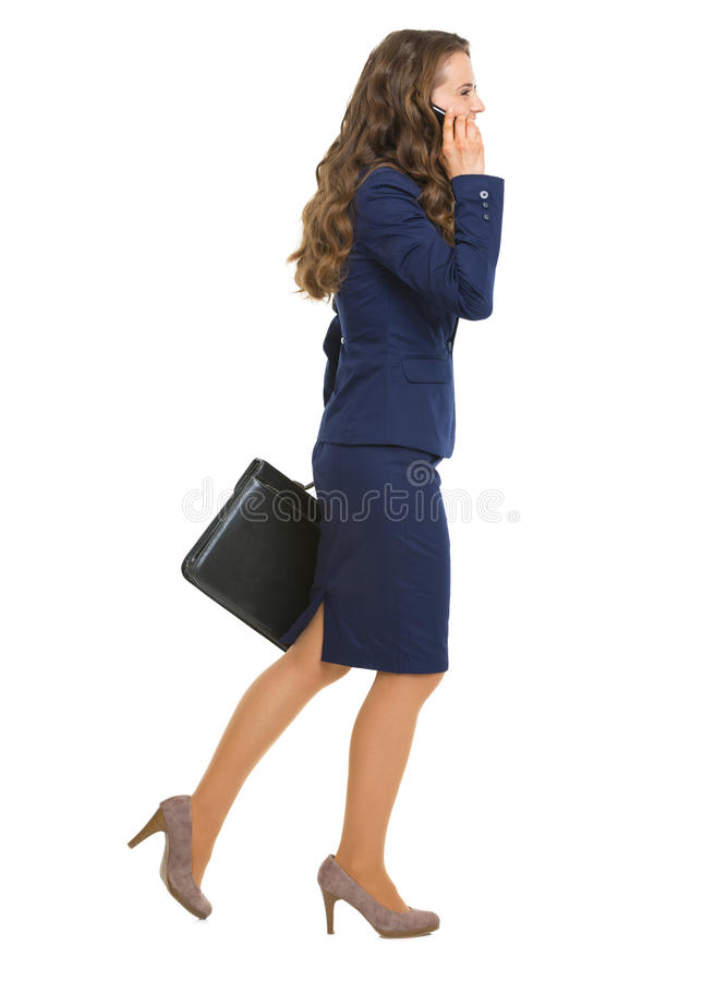 Smiling business woman going sideways talking cell phone. Smiling business woman with briefcase going sideways talking cell phone isolated on white royalty free stock images