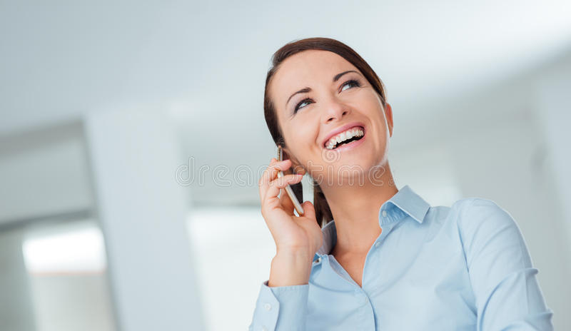 Smiling business woman having a phone call. Smiling confident business woman having a phone call with her mobile phone, office interior on background royalty free stock images