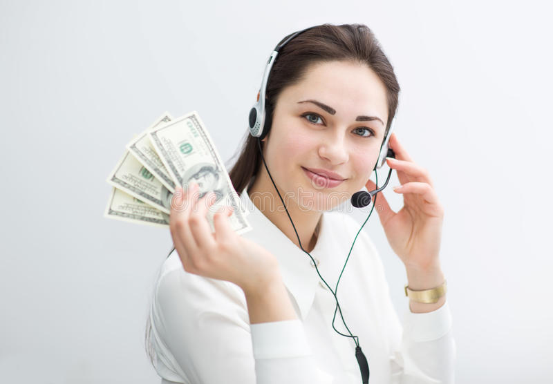Smiling business woman in headphones holds banknotes in hand royalty free stock photos