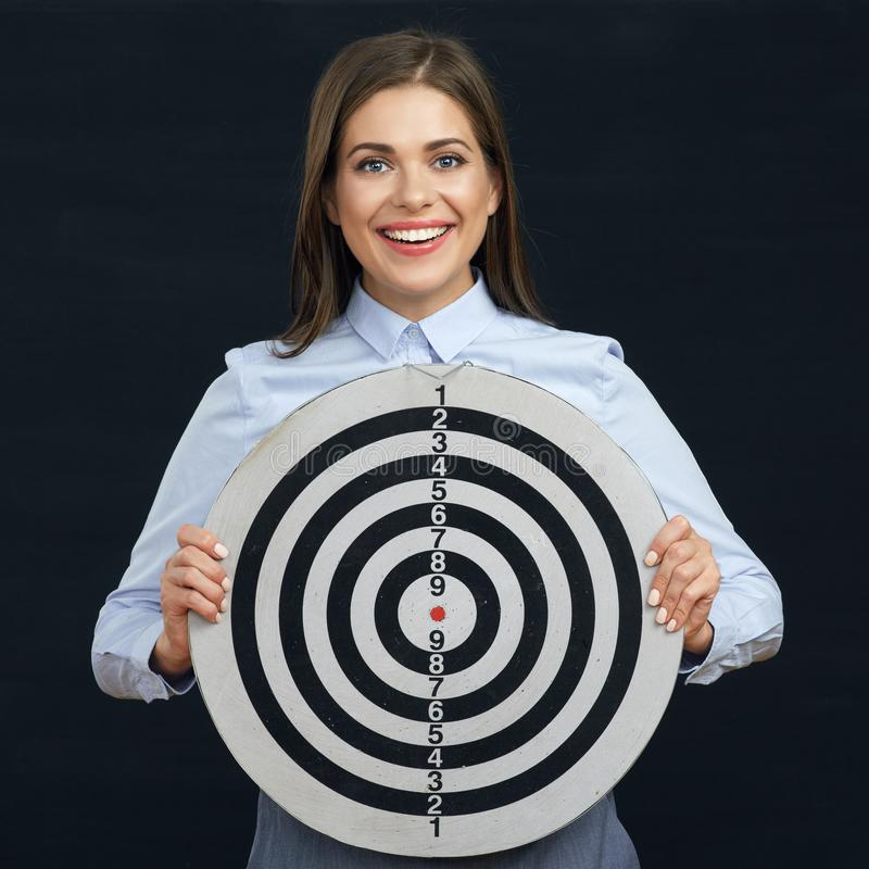 Smiling business woman holding darts target. Black background stock photography