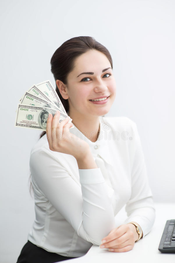Smiling business woman holding money in hand sitting at the work royalty free stock images