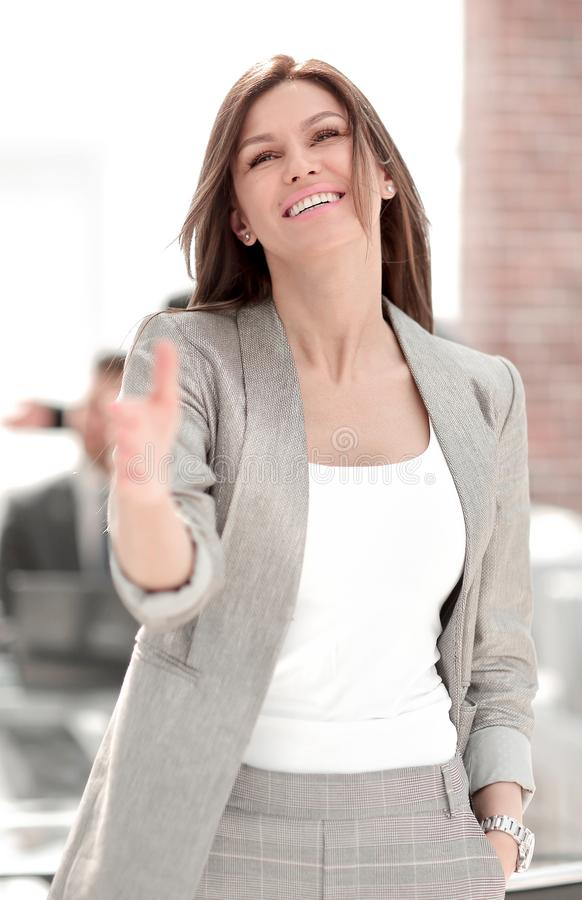 Smiling business woman holding out her hand for a handshake royalty free stock image