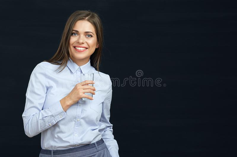 Smiling business woman holding water glass. Black background stock photography