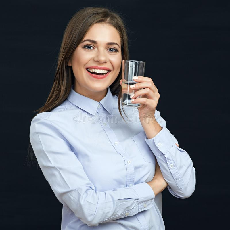 Smiling business woman holding water glass. Black background isolated royalty free stock photo
