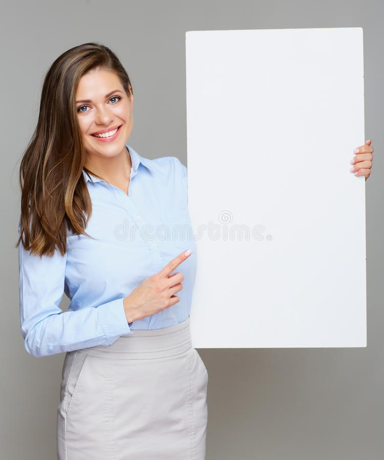 Business woman holding white big sign board and pointing finger. Smiling Business woman holding white big sign board and pointing finger at copy space. portrait royalty free stock photo