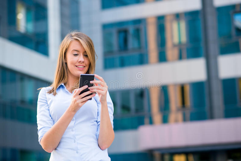 Smiling business woman listening to call on smartphone in front of her office.  stock photo