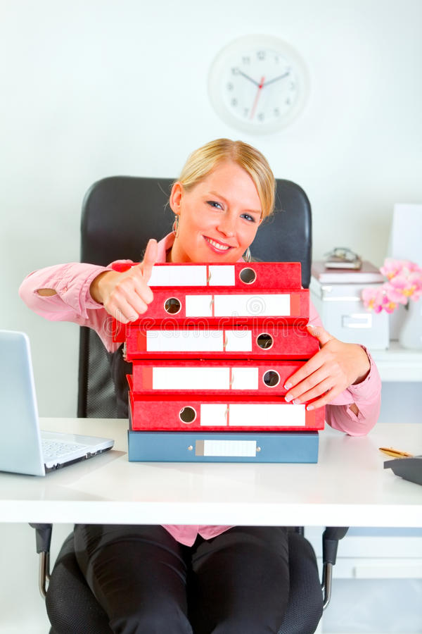 Smiling business woman with pile of folders showin. Work is done! Smiling modern business woman with pile of folders showing thumbs up stock photos