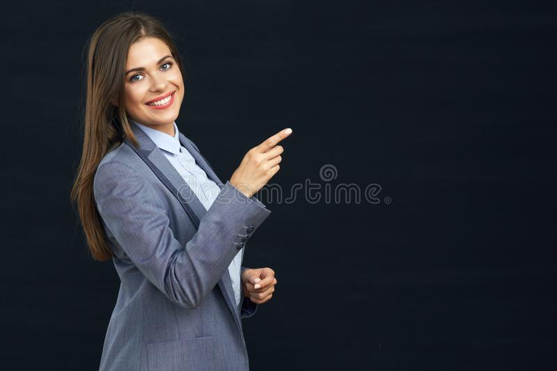 Smiling business woman pointing finger on copy space. Black background stock photo
