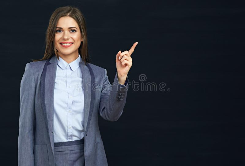 Smiling business woman pointing finger on copy space. Black background royalty free stock images