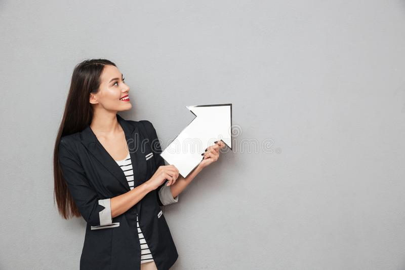 Smiling business woman pointing with paper arrow and looking up. Smiling asian business woman pointing with paper arrow and looking up over gray background stock images