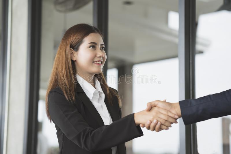 Smiling business woman shaking hands in the office building stock photo