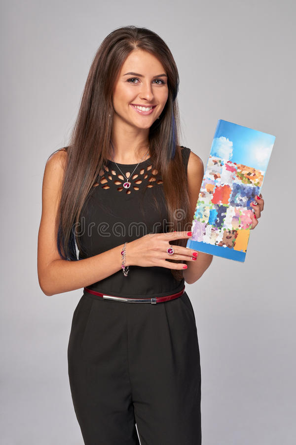Smiling business woman showing advertising brochure stock image