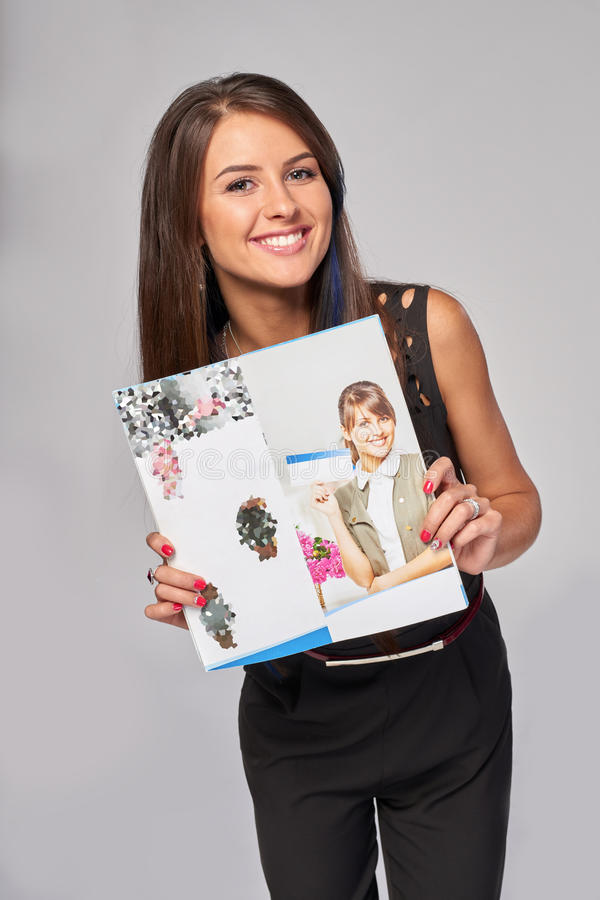 Smiling business woman showing advertising brochure royalty free stock images