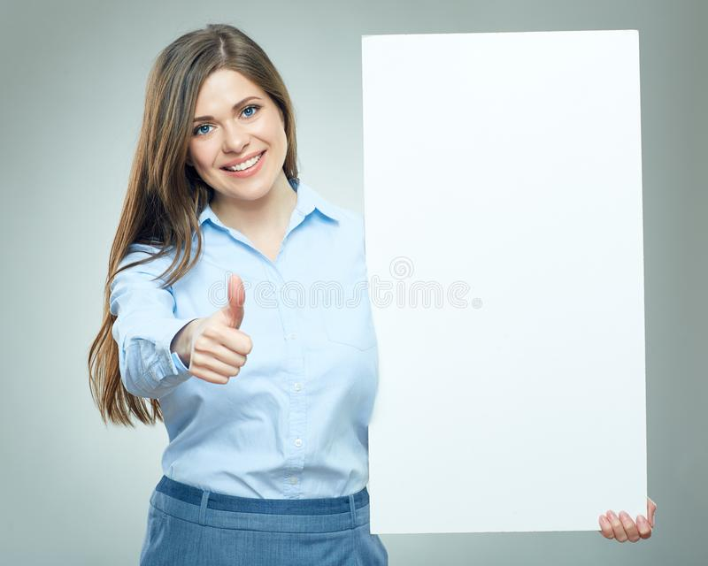 Smiling business woman showing thumb up holds white sign board stock image