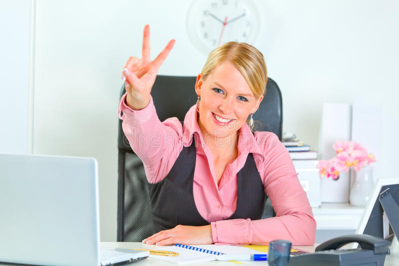Smiling business woman showing victory. Smiling modern business woman sitting at office desk and showing victory gesture stock photography