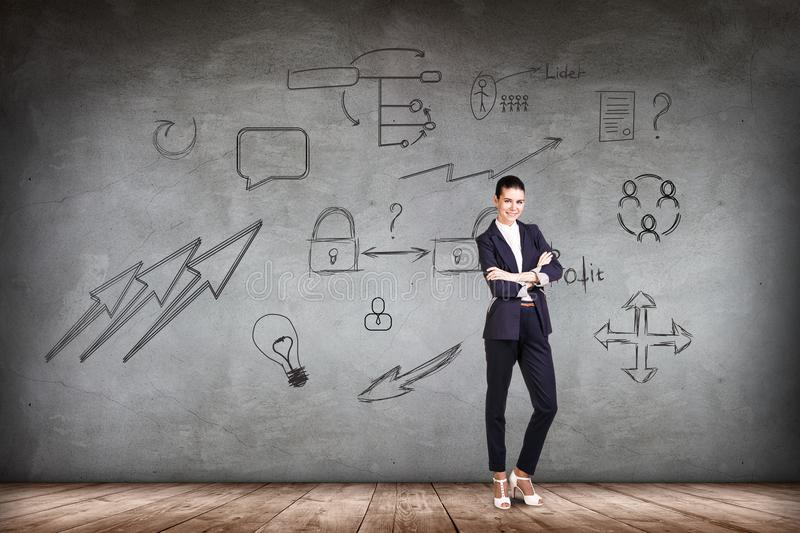 Businesswoman over wall with icons background. stock image