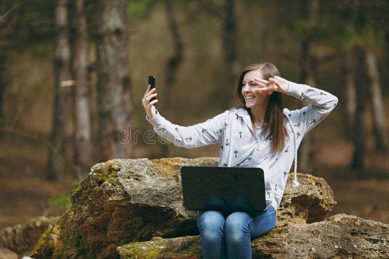 Smiling business woman or student sitting on stone with laptop doing selfie and showing victory sign on mobile phone in stock photo