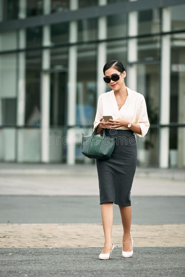 Elegant business lady. Smiling business woman walking outdoors and reading text message royalty free stock photos