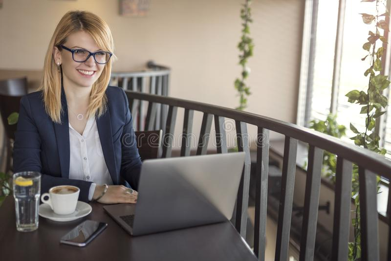 Smiling business woman is working on computer, looking for information on internet, in a coffee shop, restaurant stock photography