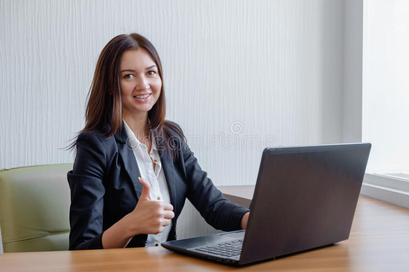Smiling business woman working on laptop and shoving thumbs up stock images