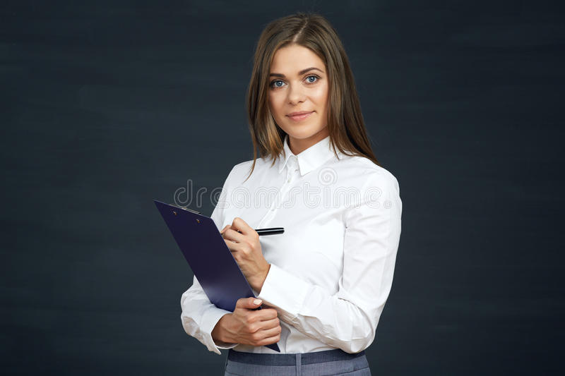 Smiling business woman writes on clipboard. royalty free stock photography