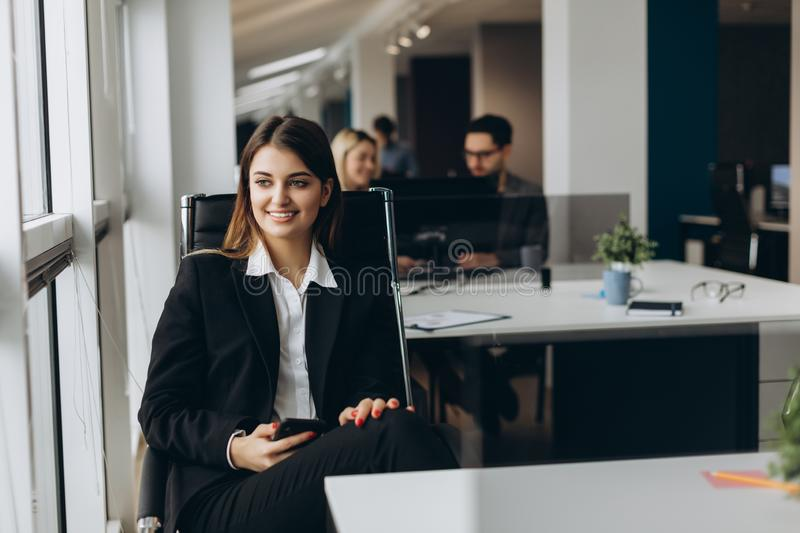 Smiling business woman using cell phone with colleagues on background in office stock photography