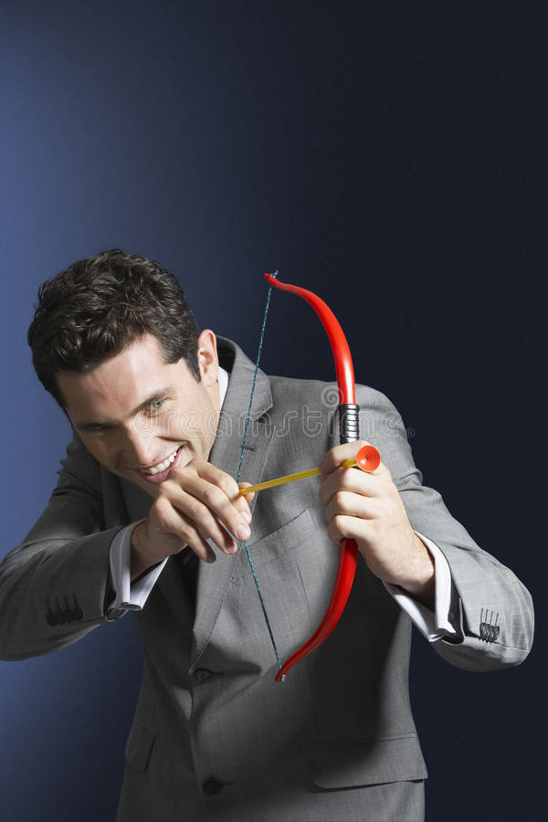 Smiling Businessman Aiming Toy Bow And Arrow stock image