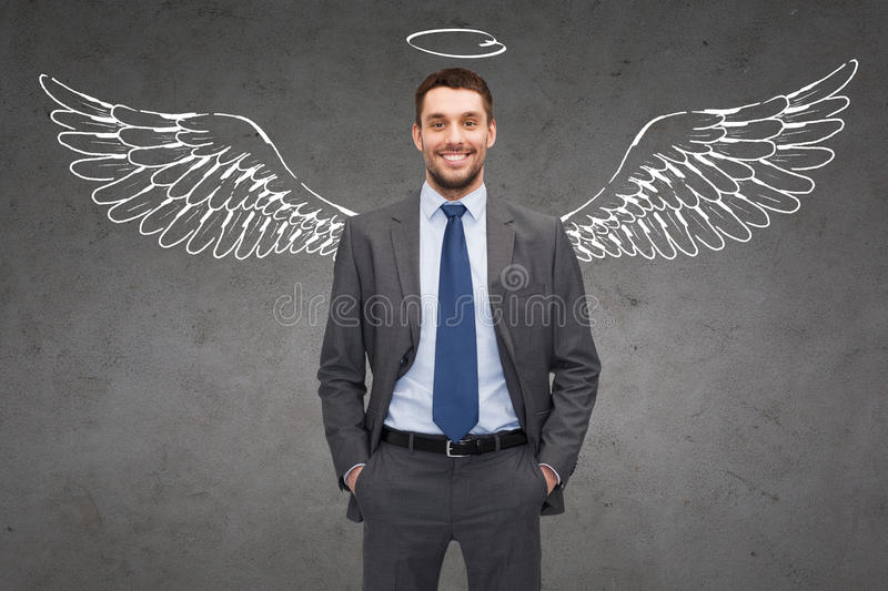 Smiling businessman with angel wings and nimbus stock photography