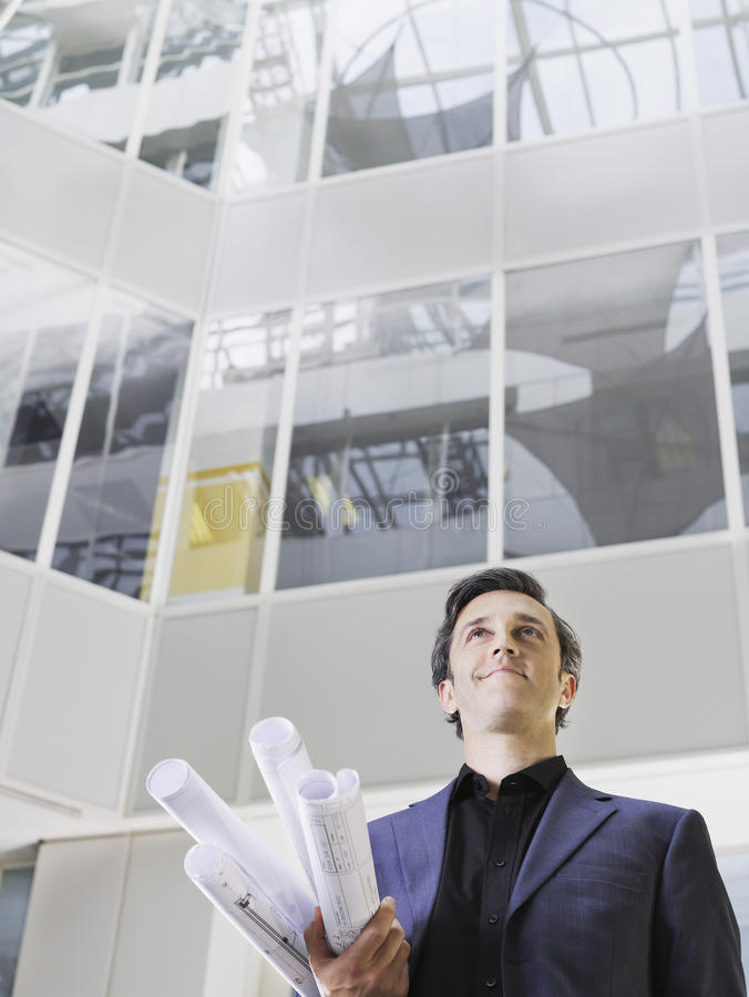 Smiling Businessman With Blueprints In Office. Low angle view of a smiling businessman holding rolled blueprints under arm in atrium of office building stock images