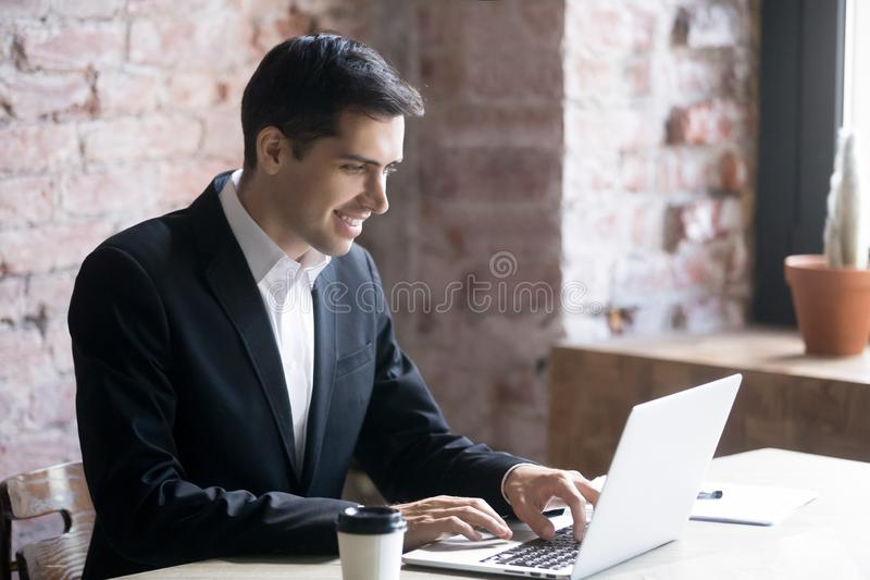 Man working on computer in office at workplace. Smiling businessman or business owner working on computer in office at workplace. Concept of successful deal royalty free stock photo